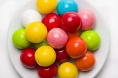 image of gumballs  - Multicolored gumballs sitting in a white plate on a white background