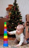 baby try to pull down colorful pyramid