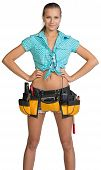 Pretty girl in shorts, shirt and tool belt with tools