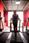 picture of cardio  - Sporty girl in sportswear walks on cardio trainer treadmill in gym  - JPG