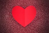 Paper heart on glittery background