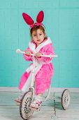 image of tricycle  - Little cute girl in pink rabbit costume sits on an old tricycle - JPG