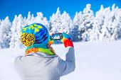 Back side of woman wearing cute colorful hat photographing beautiful winter nature, enjoying snowy landscape, happy wintertime vacation