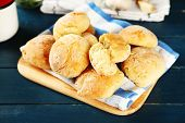 Fresh homemade bread buns from yeast dough  and jars with spices, on color wooden background