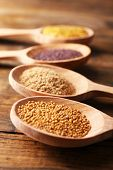 Mustard seeds, powder and sauce in wooden spoons on wooden background