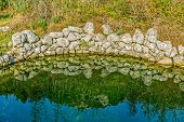pic of trough  - Ancient water trough with surrounding nature reflecting in the water at winter near village Oslje - JPG