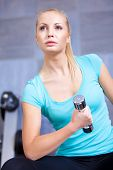 Attractive blond sporty girl doing biceps training