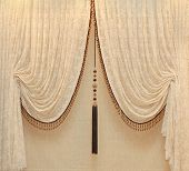 stock photo of embellish  - Vintage drapes with gold embellishments hanging from a wall - JPG