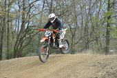 Motocross Racer Riding Down A Dirt Hill