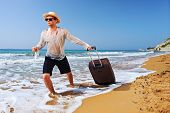 A tourist carrying a suitcase at the beach Peroulades at Corfu island