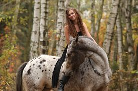 foto of appaloosa  - Young girl with appaloosa horse in autumn forest - JPG