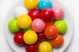 picture of gumballs  - Multicolored gumballs sitting in a white plate on a white background  - JPG