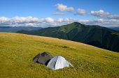 picture of tent  - Two tents on the grass field on the mountain with another mountain peak view - JPG