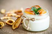 stock photo of home addition  - home sweet yogurt with dried fruit cooked in a glass jar - JPG