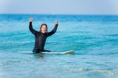 picture of board-walk  - A young surfer with his board on the beach - JPG