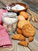foto of baked raisin cookies  - Oatmeal cookies and milk on a old wooden background - JPG
