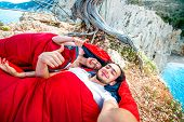 image of sleeping bag  - Young couple lying in red sleeping bags near the sea - JPG