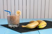 pic of light weight  - Healthy homemade Chocolate banana smoothie in glass and fresh bananas on light wooden background - JPG