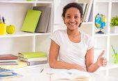stock photo of schoolgirl  - Young smiling mulatto schoolgirl in white t - JPG