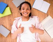 picture of mulatto  - Young smiling mulatto schoolgirl laying on the floor with some and making thumbs up - JPG