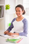 picture of schoolgirls  - Young pretty smiling schoolgirl sitting at the table and writing homework on colorful background - JPG