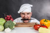 pic of chef knife  - Funny young chef with knife and vegetable on black background
