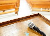 stock photo of pews  - Closeup microphone in empty church with empty pews - JPG