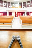 pic of pews  - Closeup microphone in empty church with empty pews - JPG