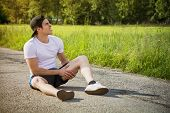 stock photo of knee-cap  - Handsome young man injured while running and jogging on road in the country in a sunny day - JPG