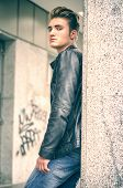pic of down jacket  - Attractive blond young man with leather jacket standing outside against pillar - JPG