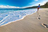 stock photo of footprints sand  - Woman at beautiful beach at Seychelles walking on sand - JPG