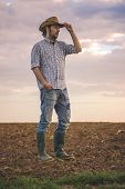 foto of farm land  - Portrait of Adult Male Farmer Standing on Fertile Agricultural Farm Land SoilLooking into Distance - JPG