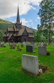 stock photo of chapels  - Wooden building of antique norwegian stave chapel and cemetery in Lom - JPG