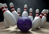 foto of bowling ball  - An arrangement of white and red used vintage bowling pins being struck by a bowling ball on a wooden bowling alley surface on a dark background - JPG