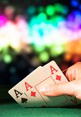 picture of poker hand  - Powerful poker hand with two aces in casino with colorful blured background