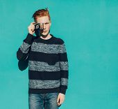 pic of redhead  - Young redhead man in a sweater and jeans standing next to green wall and taking photos vintage camera - JPG