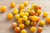 image of plum tomato  - fresh picked ripe organic colorful mini tomatoes on rustic wooden background - JPG