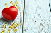 stock photo of cod  - Red heart and cod liver oil on blue wooden background - JPG