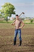 foto of hoe  - Young farmer with hoe standing in corn field in spring - JPG