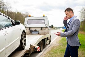 picture of trucks  - Man calling while tow truck picking up his broken car  - JPG