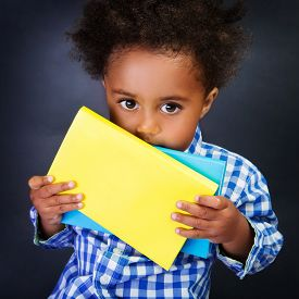 picture of schoolboys  - Closeup portrait of cute little shy American schoolboy with textbooks in hands over blackboard background - JPG