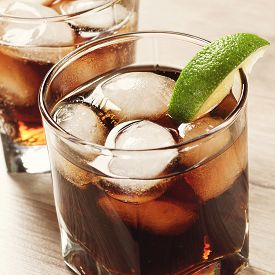 foto of coca-cola  - Cocktail with cola and ice on wooden table - JPG