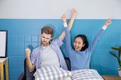 Cute Loving Couple Is With Gesture In Sofa - Man And Woman Are Sitting Smiling And Glad With Success poster