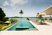 Infinity Swimming Pool Overlooking At A Lake, Bordered By Palm Trees, Lounge Chairs And Umbrella, In poster