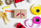 Christmas gifts preparation on white table. Gift bix with red santa hat, gift box and colorful ribbon
