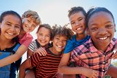 Six pre-teen friends piggybacking in a park, close up portrait poster