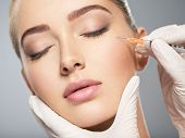 Woman getting cosmetic injection of botox near eyes, closeup. Woman in beauty salon. plastic surgery poster
