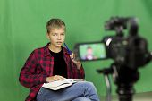 Young Boy Blogger Records Video On A Green Background poster