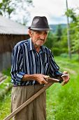 Old Rural Man Sharpening Scythe