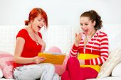 Excited young girlfriends reading letter with good news